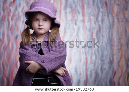 Gorgeous little girl in violet coat looking at the camera.