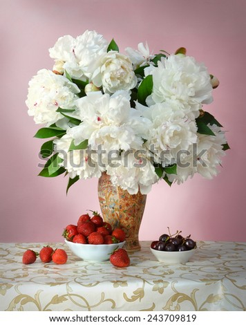 Gorgeous lush white peonies with green leaves in porcelain vase with Chinese painting on openwork tablecloth with golden pattern and dishes with sweet red strawberries and juicy dark burgundy cherries