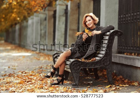 Shutterstock Gorgeous middle aged woman sitting on bench in autumn park