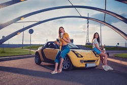 Gorgeous models in casual outfit are enjoying drinks in paper cups and hamburgers while sitting on the hood of yellow car roadster. Fast food