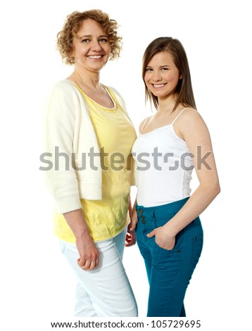 Gorgeous mother and daughter posing in front of camera. Smiling