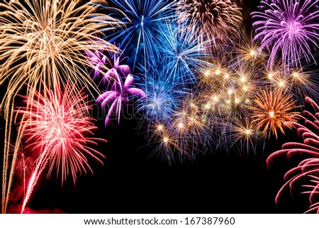 Gorgeous multi-colored fireworks display on black background with copyspace
