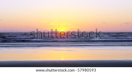 Gorgeous ocean sunset with yellow, purple and pink colors glowing on ocean waves and sandy beach