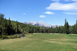 Gorgeous par 4 on a golf course surrounded by forest and big mountains in the background, on a beautiful sunny day in Kananaskis, Alberta, Canada.
