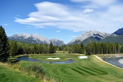 Gorgeous par 3 on a golf course surrounded by forest and big mountains in the background, on a beautiful sunny day in Kananaskis, Alberta, Canada.