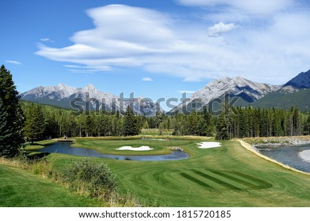 Gorgeous par 3 on a golf course surrounded by forest and big mountains in the background, on a beautiful sunny day in Kananaskis, Alberta, Canada. Foto stock ©
