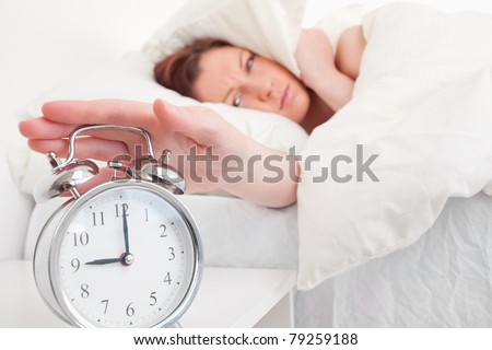 Gorgeous red-haired female waking up thanks to an alarm clock in the bedroom