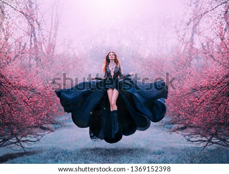 gorgeous red-haired hot woman in long flying black dress fluttering, witch turns into crow, dark queen in frozen spring flowering forest, levitation and flight, open breasts and bare sexy legs #1369152398
