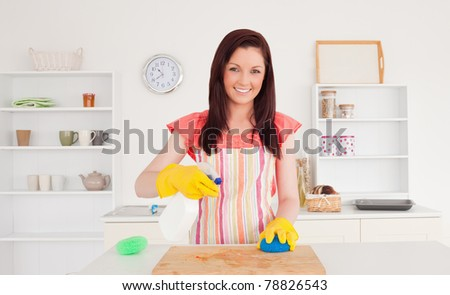 Gorgeous red-haired woman cleaning a cutting board in the kitchen in her apartment