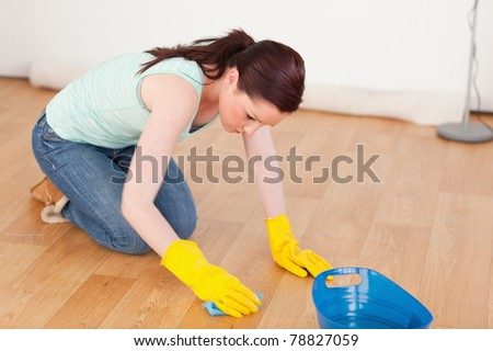 Gorgeous red-haired woman cleaning the floor while kneeling at home