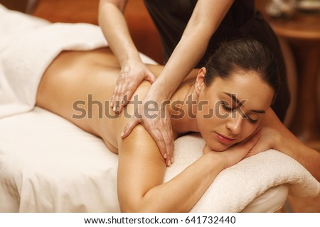 Gorgeous relaxed woman lying with her eyes closed enjoying body massage at spa center professional masseur masseuse massaging relaxing therapy beauty recreation wellness wellbeing health vitality