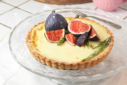 gorgeous round french classic homemade shortcake pastry dough vanilla custard tart cake decorated with figs and rosemary on glass stand near with retro fork on grey table cloth. Insta food photo style