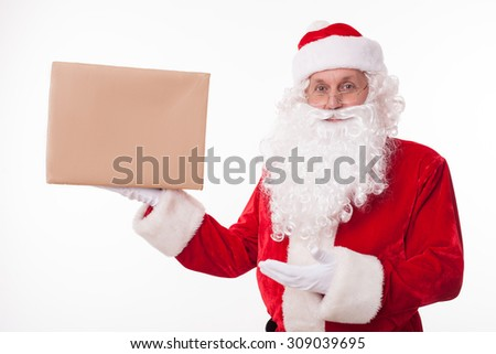 Gorgeous Santa Claus is standing and holding a box of preset. He is presenting it with another hand. The man is looking forward and smiling