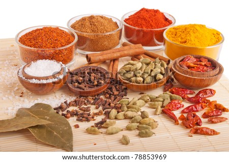 gorgeous setting with cooking spices and herbs (bay leaves, chili powder, cloves, cardamom pods, cinnamon sticks, garam masala, paprika, piri piri, salt, turmeric) on a wooden mat (isolated on white)