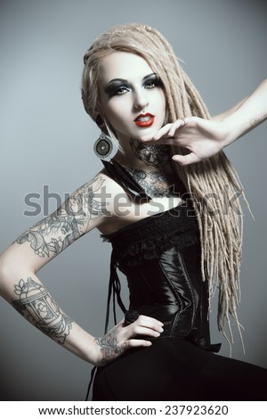 Gorgeous sexy girl with black make-up and long dreadlocks. Gothic style. Fashion. Cosmetics, hairstyle. Tattoo.