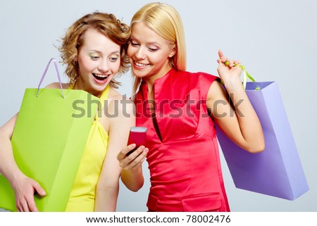 Gorgeous shoppers reading sms on mobile phone