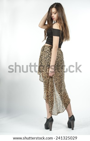 Gorgeous slim young brunette with her hair down wearing high waisted black leopard skirt with a black top on a white background in a studio.