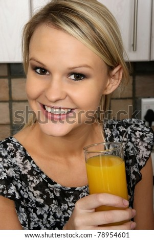 Gorgeous smiling blond girl with a glass of orange juice - stock photo