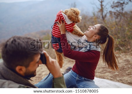Gorgeous smiling Caucasian brunette sitting on blanket and posing with her dog while her boyfriend taking picture of them. Picnic at autumn concept.
