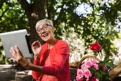 Gorgeous smiling caucasian senior woman with blonde short hair sitting on bench in park and make video call with digital tablet.