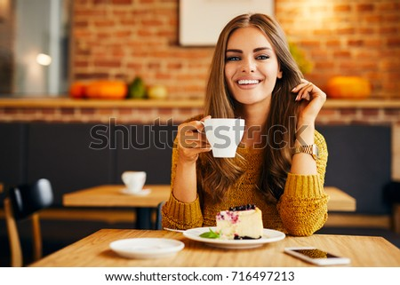 Gorgeous smiling young woman looking straight at camera while drinking coffee and eating cake in a cafe #716497213