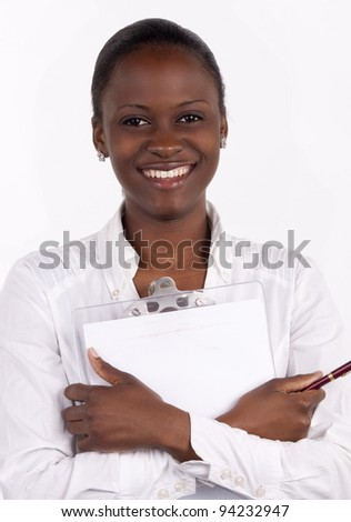 Gorgeous South African woman holding a notepad and pen to her chest, with a big smile.