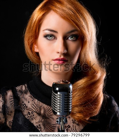 Gorgeous stylish redhead woman with retro microphone