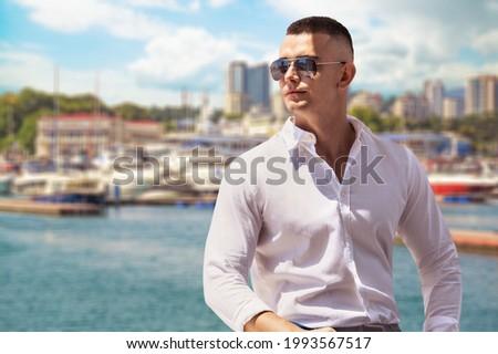 Gorgeous stylish young man wearing fashionable shirt and sunglasses. City style.