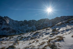 Gorgeous sunbeams in clear blue sky over High Tatra Mountains. Winter in Poland. Silhouettes of rocky peaks covered with snow. Selective focus on withered grass under the snow, blurred background.