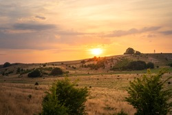 Gorgeous sunset over valley of nature reserve Hilleshogs dalar during summer in south part of Sweden. Selective focus.