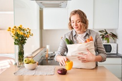 Gorgeous vegetarian woman unloadings a bag of fruits and vegetables after picking up the delivery of groceries. Stock photo