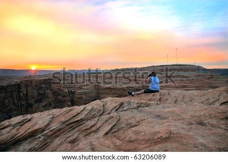 Gorgeous vibrant sunset with vivid colors of orange, yellow, and pink from the top of Glen Canyon, near the dam