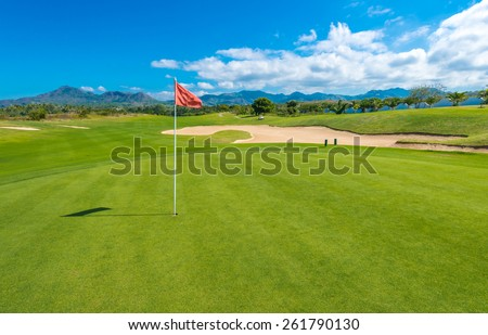 Gorgeous view at the beautiful golf course with sand bunker and red flag.