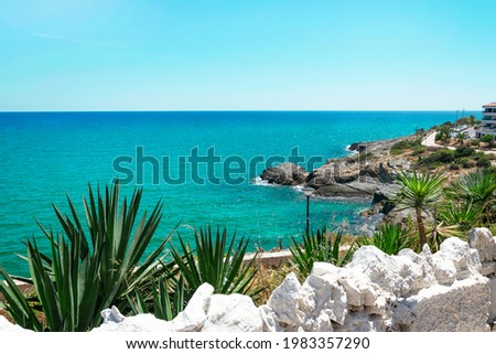 gorgeous view of the Mediterranean from the mountains to the palms, white stones and houses. Azure sea and coast with tropical plants, with a hotel in the distance on the rocks Foto stock ©