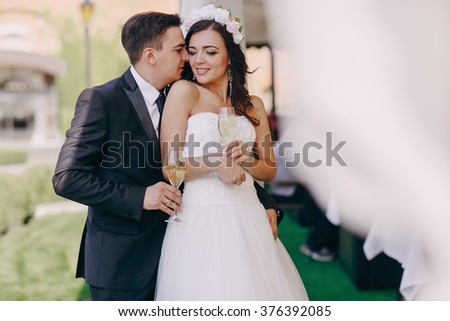 gorgeous wedding couple enjoys champagne sitting in the restaurant #376392085