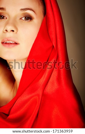Gorgeous woman in red satin looking at camera