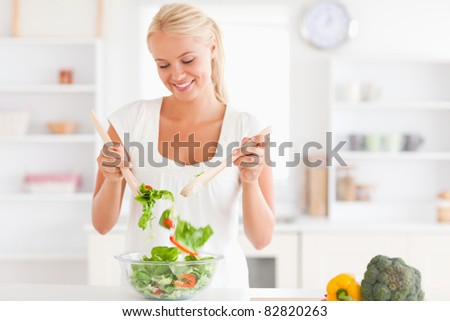 Gorgeous woman mixing a salad in her kitchen