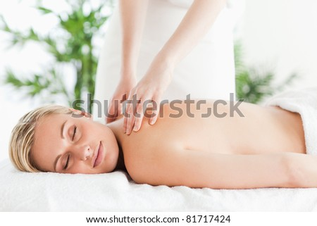 Gorgeous woman relaxing on a lounger during massage with eyes closed in a wellness center