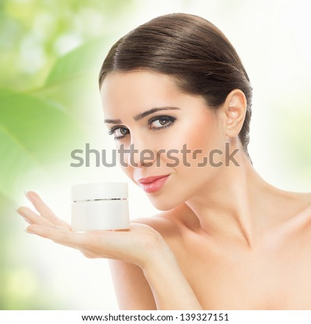 Gorgeous woman smiling and holding face cream