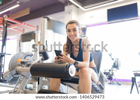 Gorgeous woman using mobile phone while sitting on exercise machine at health club