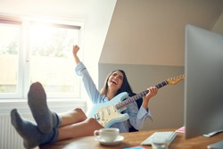 Gorgeous woman with guitar shouting with joy while bare sock feet are on desk beside computer