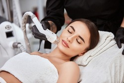 gorgeous woman with perfect skin and eyebrown receiving hair removal on her face, pretty girl in spa doing procedures for her lovely face