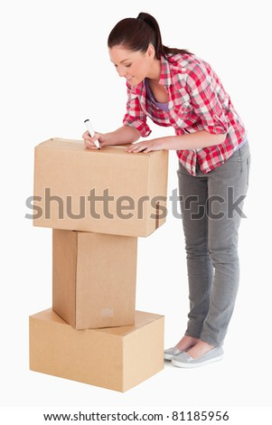 Gorgeous woman writing on cardboard boxes with a marker while standing against a white background