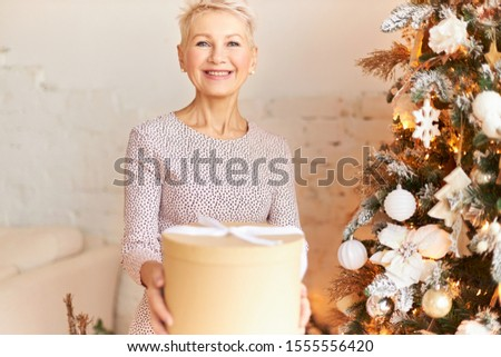 Gorgeous 50 year old European female wearing stylish dress wishing you Happy New Year, passing box with gift, looking at camera with radiant smile, being in festive mood. Holidays, festivity and party