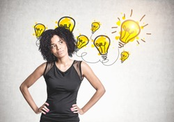 Gorgeous young African American woman wearing black jeans is standing with her hands on the waist and thinking. Yellow light bulbs on a concrete wall. An idea concept