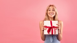 Gorgeous young blonde model holding gift box over pink studio background, panorama with free space. Pretty millennial lady with Woman's Day or birthday present. Shopping for spring holiday concept