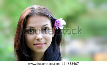 gorgeous young brown-eyed girl with flower in her hand. Close-up headshot