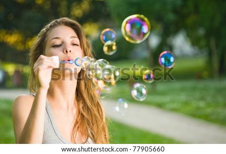 Gorgeous young brunette girl blowing soap bubbles in sunlit park.