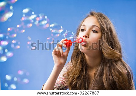 Gorgeous young brunette girl blowing soap bubbles on blue background.
