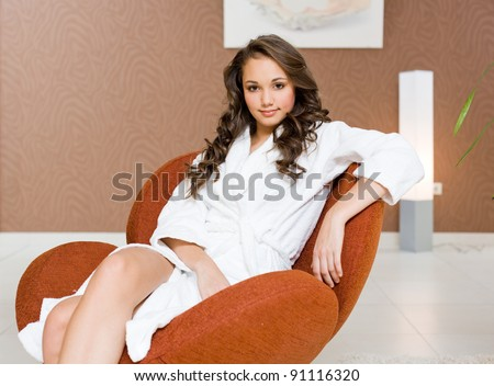 Gorgeous young brunette girl relaxing after spa in white bathing robe, in luxurious environment.